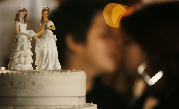A gay couple kisses next to their wedding cake during a symbolic group wedding on Valentine's Day in Lima February 14, 2011. The wedding was organized by the local gay community to create a discussion about the illegality of gay marriages in Peru. REUTERS/Enrique Castro-Mendivil (PERU - Tags: SOCIETY)